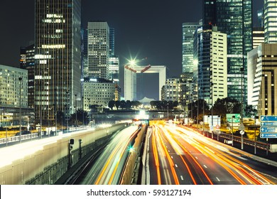 Skyscrapers in Paris business district La Defense. European night cityscape with dynamic street traffic, car lights and glass facades of modern buildings. Economy, finances, transport concept. Toned
