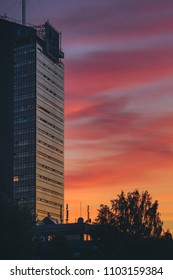 Skyscrapper in colorful sunset at late summer evening in Riga, Latvia. Sky painted orange, yellow and red. Breathtaking sky.