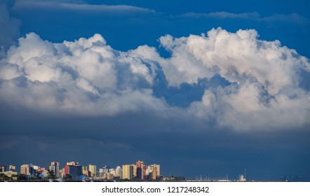 Skyscrappers near sea with stormy clouds hat over them
