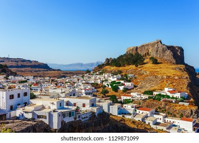 Skyview landscape photo Lindos town and castle on Rhodes island, Dodecanese, Greece. Panorama with ancient castle and town with white buildingsr. Famous tourist destination in South Europe
