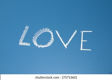 Skywriting Love on a blue sky with sun nearby
