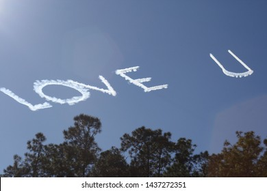 Skywriting quote love you. Plane written love u against blue sky visible above green trees. Affectionate writing brings happiness. Makes you think of valentines day, anniversary, etc. sky writing