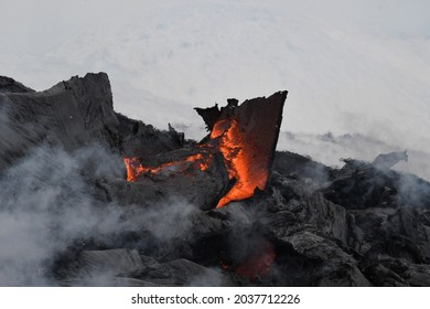 A slab of lava crust is overturned in a lava flow at Fagradalsfjall, Iceland. The lava surface is black, with red, molten lava visible beneath and steam rising. Snowy hills in the background.