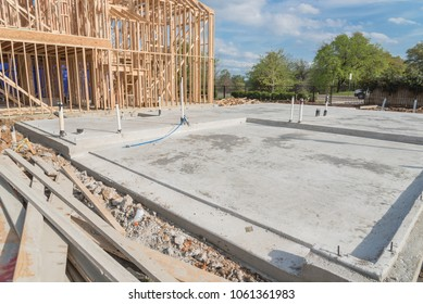 Slab-on-grade foundation footing timber frame house under construction in Irving, Texas, USA. Shallow raft structural engineering transfers building loads to earth very near to surface, pile of panels
