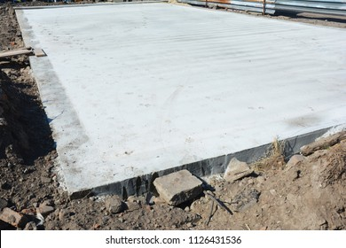 Slab-on-grade foundation on house construction site. Monolithic slabs are foundation systems constructed as one single concrete pour that consists of a concrete slab.