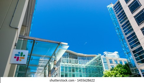Slack Technologies logo on facade of software company headquarters with high rise citiscape background - San Francisco, California, USA - July 12, 2019
