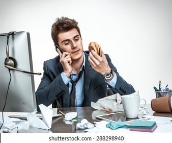 Slacker man talking on the phone while eating at work / modern office man at working place, sloth and laziness concept