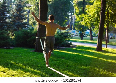 Slackline in the summer park against a background of green grass