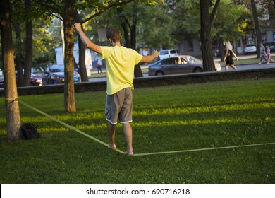 Slackline in the summer park Against the background of city bustle