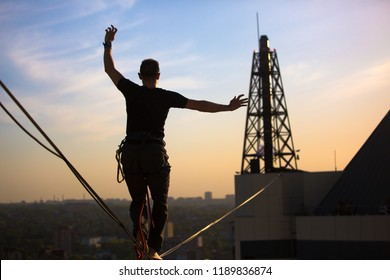 Slackliner balancing on tightrope between tall buildings