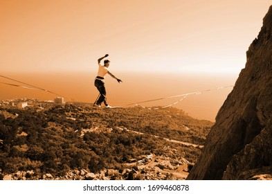 Slacklining. Man highlining on a slope at a height near a cliff overlooking the sea coast background.