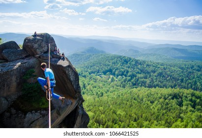 Slacklining, man walks the line at high altitude above the forest