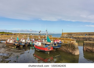 Slade, Eire - 16th October 2012: The Inner Harbour entrance at Slade Harbour, a small Fishing Village in County Wexford, Southern Ireland, with Fishing Boats lying on the Silt.