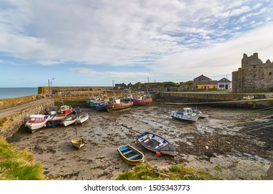 Slade, Eire - 16th October 2012: Boats lie on the silt at low tide in the inner harbour of Slade, overlooked by the Castle and ruins.