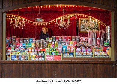 SLAGHAREN, NETHERLANDS - MAY 19, 2013: Front view of a female seller in an old traditional outdoor illuminated market candy shop store. Many assorted candy sticks and items in Slagharen May 19, 2013.