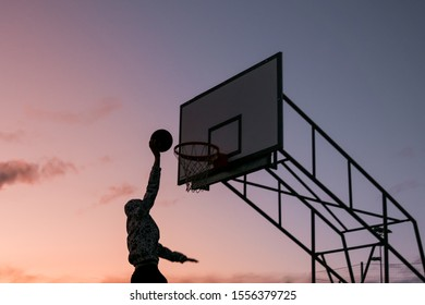 slam dunk basketball isolated sunset. Scoring silhouette dunking man outdoors