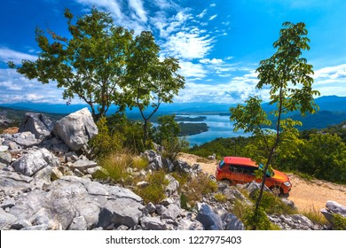 Slansko lake, Niksic, Mount Trebjesa, Montenegro - August 2014. Skoda Fabia II car on a dirt road in front of a hill, large stones and green trees and a colorful lake and blue sky with clouds.