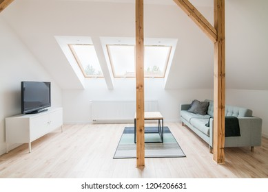 Slanted ceiling living room. Modern bright flat apartment in the attic