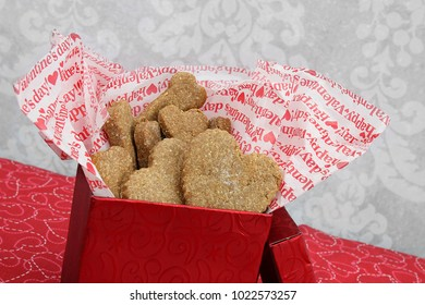 A slanted red box of homemade dog cookies, bone and heart shaped, for Valentine's Day.