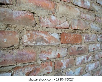 SLANTED VIEW OF A CRUDELY BUILT BRICK WALL