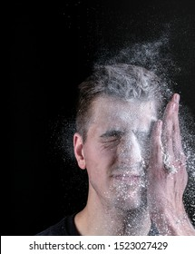 Slap on the face with a palm. Flour is poured into the palm. Frozen face shot on black background.