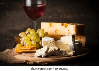 Slate board with various cheese and a glass of red rose wine. Brie. Camembert. Gouda, Maasdam, Roquefort, Cheddar and grapes on a wood with nuts, honey, crackers, blue cheese. Italian, French cheese.