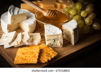 Slate board with various cheese and a glass of red rose wine. Brie. Camembert. Gouda, Masdaam, Roquefort, Cheddar and grapes on a wood with nuts, honey, crackers, blue cheese. Italian, French cheese.