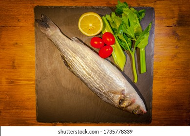 Slate dish with sea bass, lemon, celery and tomatoes on wooden background. Concept: cuisine based on fish