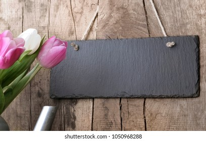 slate hung by sting at a rustic plank with tulips on the side Note à l'équipe de