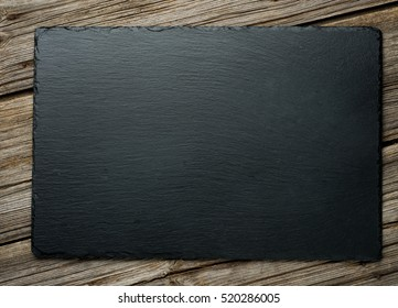 Slate over old wooden background