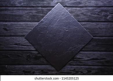 Slate over old wooden black background