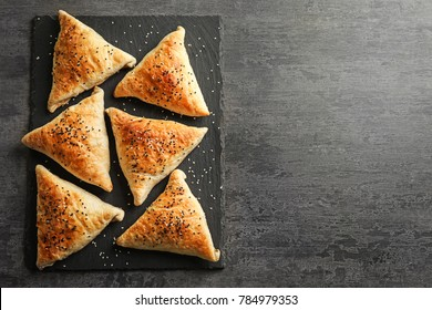 Slate plate with delicious samosas on grey background