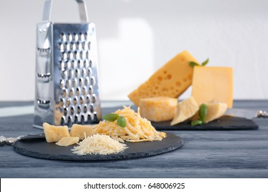 Slate plate with different grated cheese on table