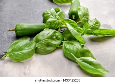 Slate plate with fresh basil and peppers on grey background