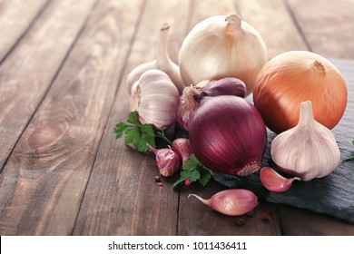 Slate plate with fresh garlic and onion on wooden table, closeup