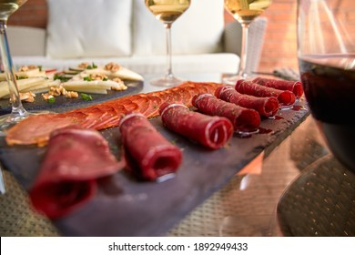 Slate plate with ham and cold cuts accompanied with glasses of wine