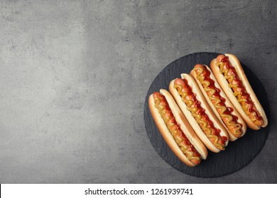 Slate plate with hot dogs on grey background, top view. Space for text
