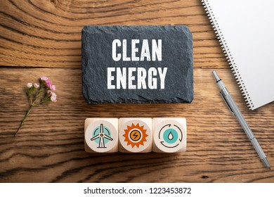"""slate plate with message """"clean energy"""" and cubes with related icons on wooden background"""