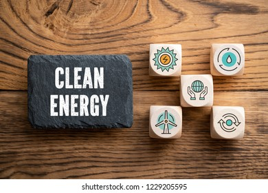 "slate plate with message ""clean energy"" and cubes with related icons on wooden background"