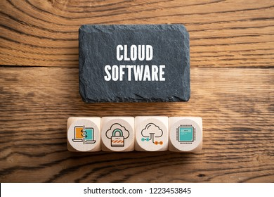 """slate plate with message """"cloud software"""" and cubes with related icons on wooden background"""