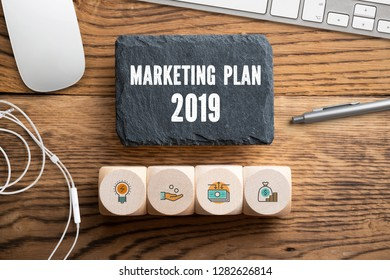 "slate plate with message ""marketing plan 2019"" on wooden background surrounded by office stuff"
