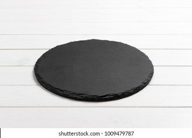 Slate plate on table. black slate stone on wooden background. copy space.