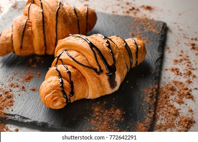Slate plate with tasty croissants on table, closeup