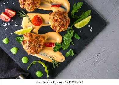 Slate plate with tasty sausage balls and sauces on table, top view