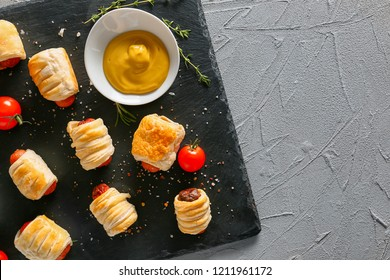 Slate plate with tasty sausage rolls and sauce on table, top view