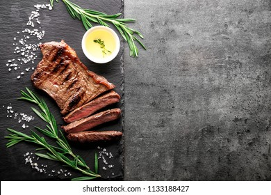 Slate plate with tasty steak, herbs, oil and salt on grey background