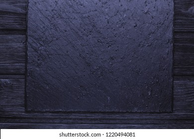 Slate with water drops over old wooden black background