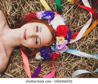 Slav girl with wreath lying at field