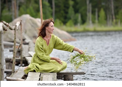 Slav woman by the water with a wreath in her hands