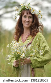 Slav woman in a green dress with a wreath of daisies in her hair and a bouquet of daisies in her hands